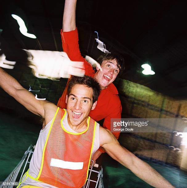 close-up of two young men riding on a shopping cart (blurred)
