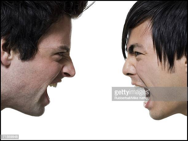 Close-up of two young men shouting at each other