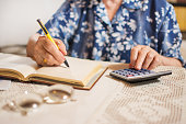 Close-up of unrecognizable senior woman doing finances at home.