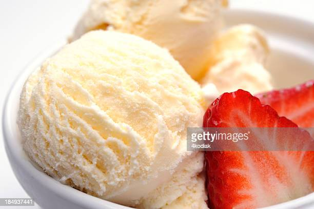 Close-up of vanilla ice cream scoops and strawberry slices