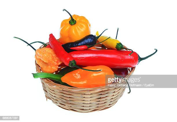 Close-Up Of Various Chili Peppers In Wicker Basket On White Background