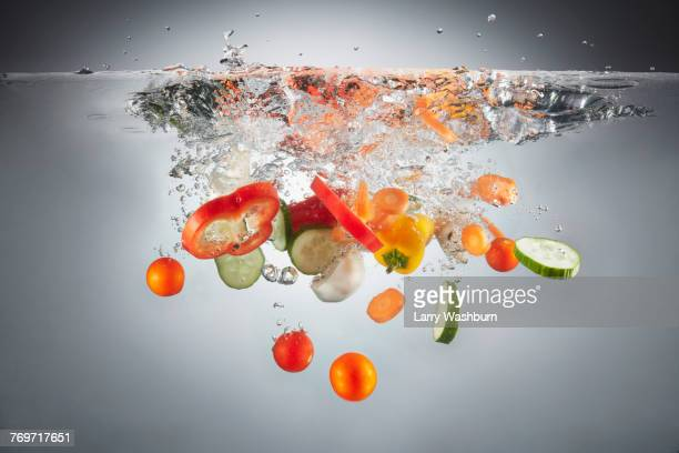 Close-up of various chopped vegetables in splashing water
