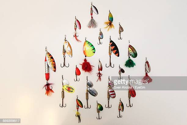 Close-Up Of Various Colorful Fishing Hooks Against White Background