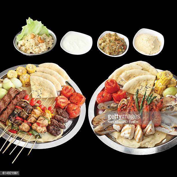 Close-Up Of Various Grilled Foods In Plates Against Black Background