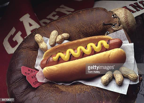 Closeup of various items associated with the American pasttime of baseball a hotdog a baseball and glove game tickets peanuts and baseball fan...