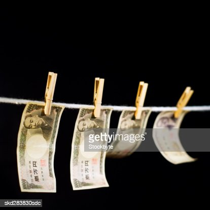 Close-up of various Japanese yen notes hanging on clothesline : Stock Photo