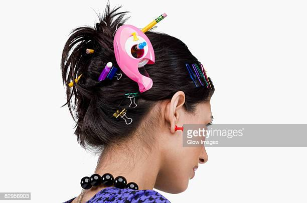 Close-up of various office supply items in a young woman's hair