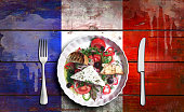 Closeup of vegetable salad on Flag of France, painted on a plank background.