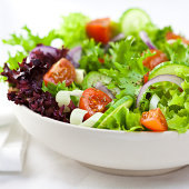 A close up of a mixed vegetable salad, offset to the right.  The salad is mostly green leafy lettuce.  The salad also features red leafy lettuce, rings of onion, quartered tomatoes, and sliced cucumbe