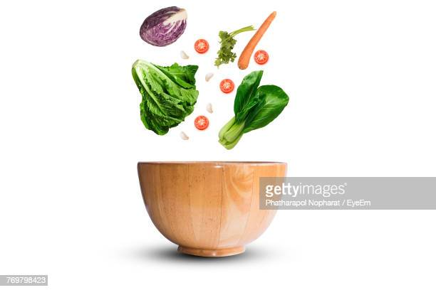Close-Up Of Vegetables Falling In Bowl Against White Background