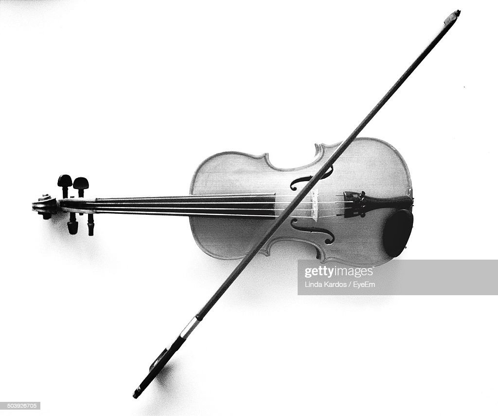Close-up of violin and bow over white background