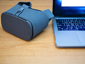 close-up of VR goggles next to laptop for virtual reality experience or software development for augmented reality features