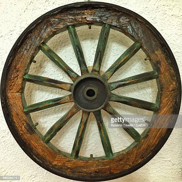 Close-Up Of Wagon Wheel Against Wall