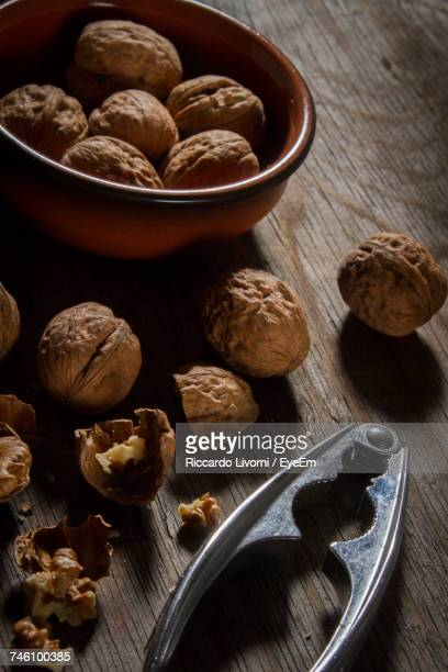 Close-Up Of Walnuts And Nutcracker On Wooden Table