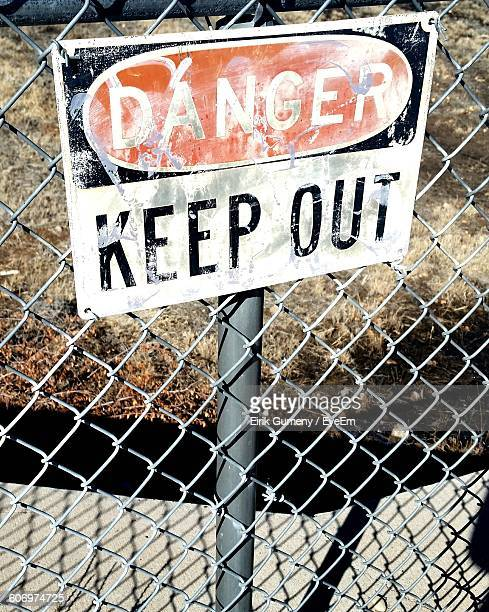 Close-Up Of Warning Sign On Chain Link Fence