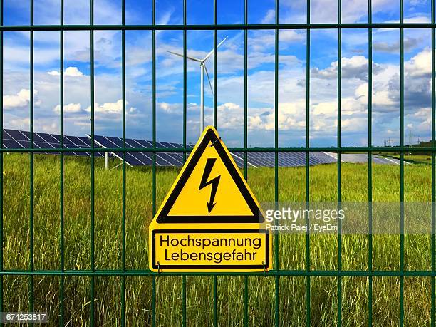 Close-Up Of Warning Sign On Railing Against Farm And Sky