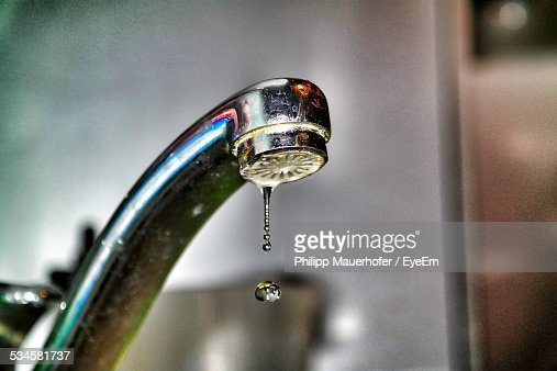 Close-Up Of Water Droplet Dripping From Kitchen Faucet