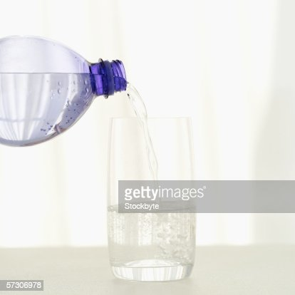 Close-up of water pouring from a bottle into a glass : Stock Photo