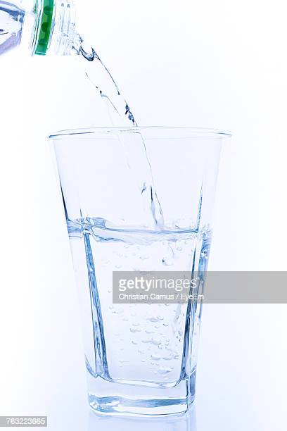 Close-Up Of Water Pouring In Drinking Glass Against White Background
