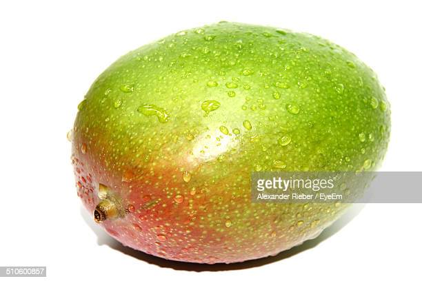 Close-up of waterdrops on mango over white background