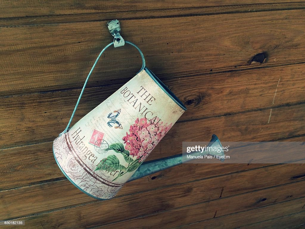 Close-Up Of Watering Can Hanging On Wooden Wall