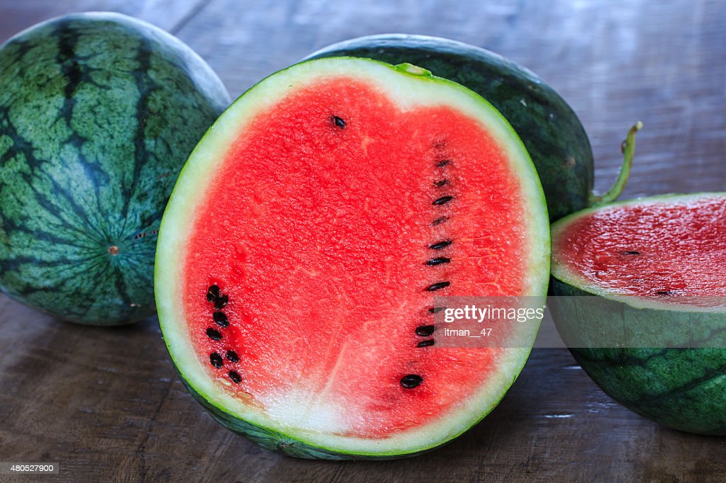 Closeup of Watermelon (Whole and Slice) on Wooden Table. : Stock Photo