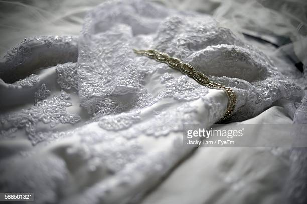 Close-Up Of Wedding Dress On Bed At Home