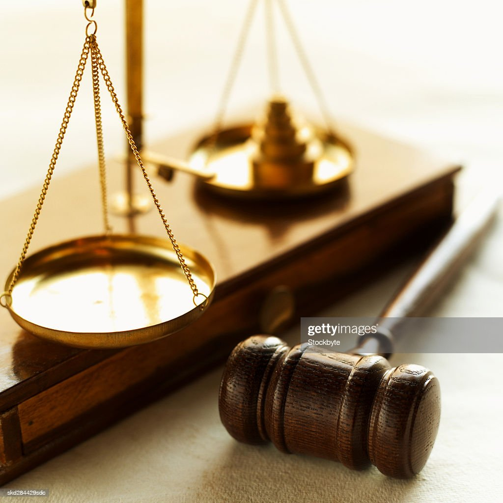 Close-up of weights balancing scales of justice with gavel beside it : Stock Photo