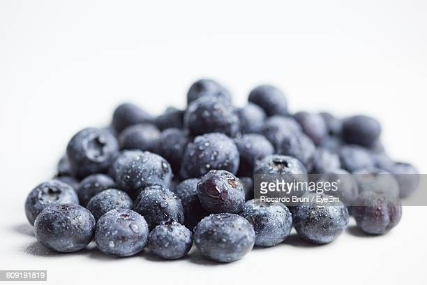 Close-Up Of Wet Blueberries Against White Background