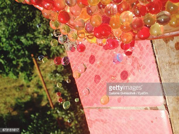 Close-Up Of Wet Colorful Silicone Balls Falling From Container