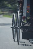 Closeup of the wheels on an Amish buggy rolling down the road in Lancaster, Pennsylvania.  You can almost see the wheels moving. The buggy sports a 'no gas' bumper sticker.
