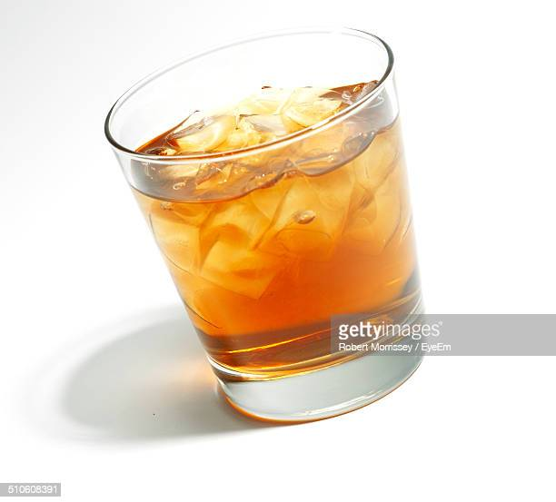Close-up of whiskey glass over white background