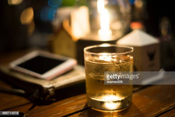 Close-up of whisky glass out by business man using smart-phone