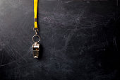 Close-up of a metal sports whistle with lanyard hanging on blackboard.