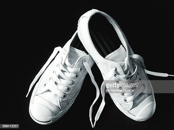 Close-Up Of White Canvas Shoes On Black Background
