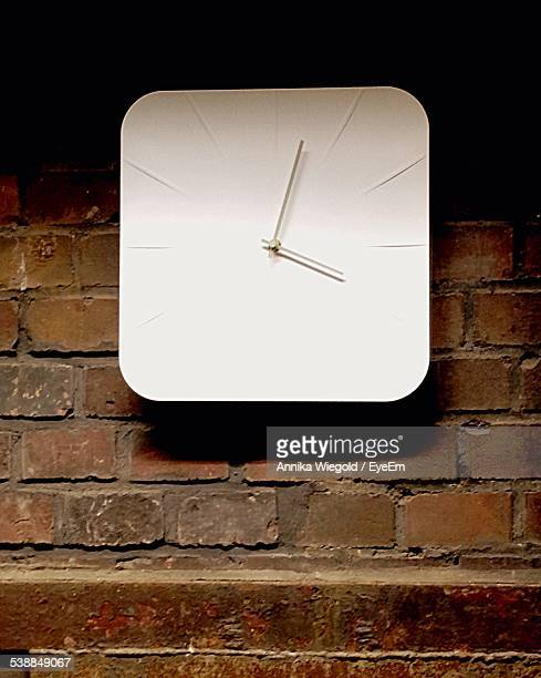 Close-Up Of White Clock On Brick Wall