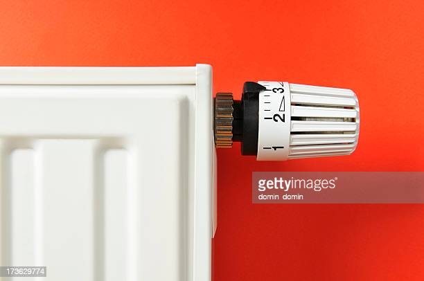 Close-up of white thermostat and radiator on red background
