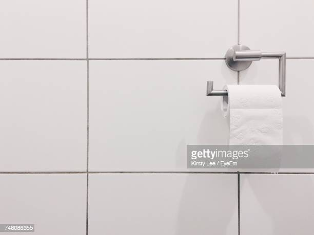 Close-Up Of White Tiled Wall With Toilet Paper
