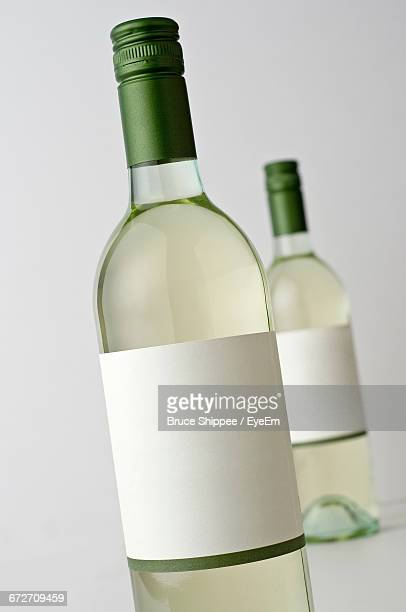 Close-Up Of Wine Bottles Against White Background
