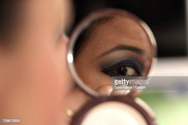 Close-Up Of Woman Applying Eyeliner Seen From Hand Mirror