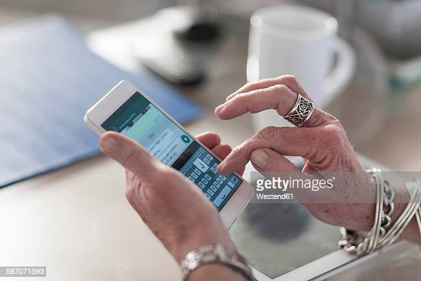 Close-up of woman at desk text messaging