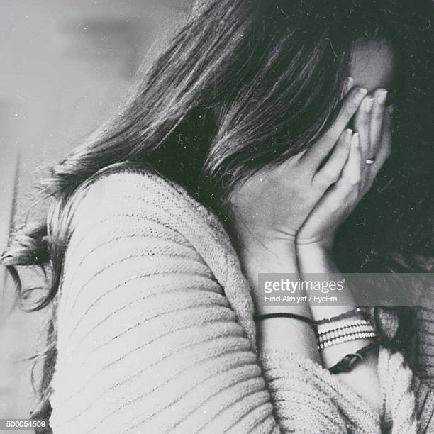Close-up of woman covering face with hands