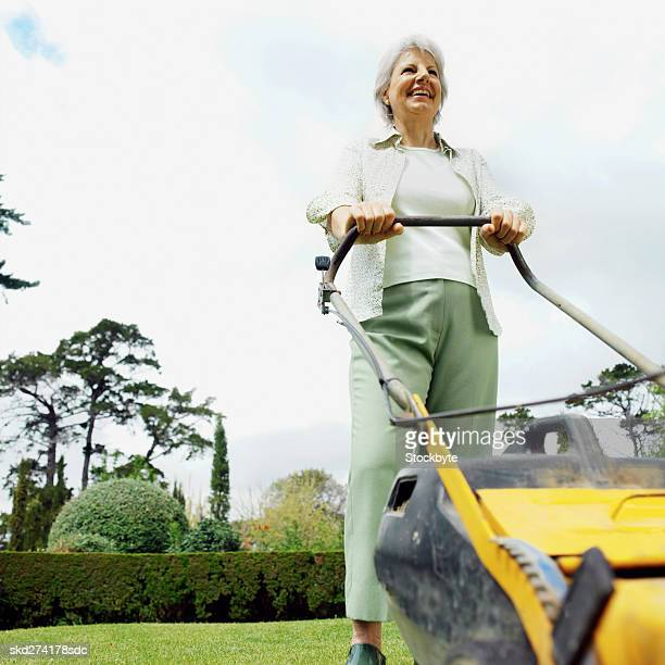 Close-up of woman cutting grass with lawn mower