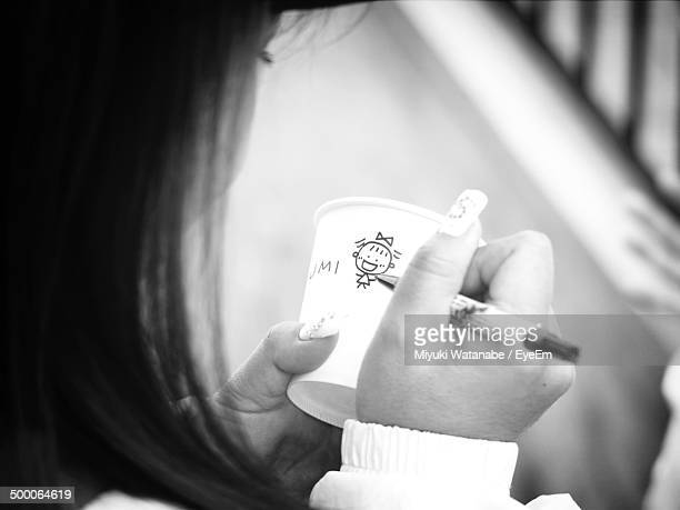 Close-up of woman drawing on disposable cup