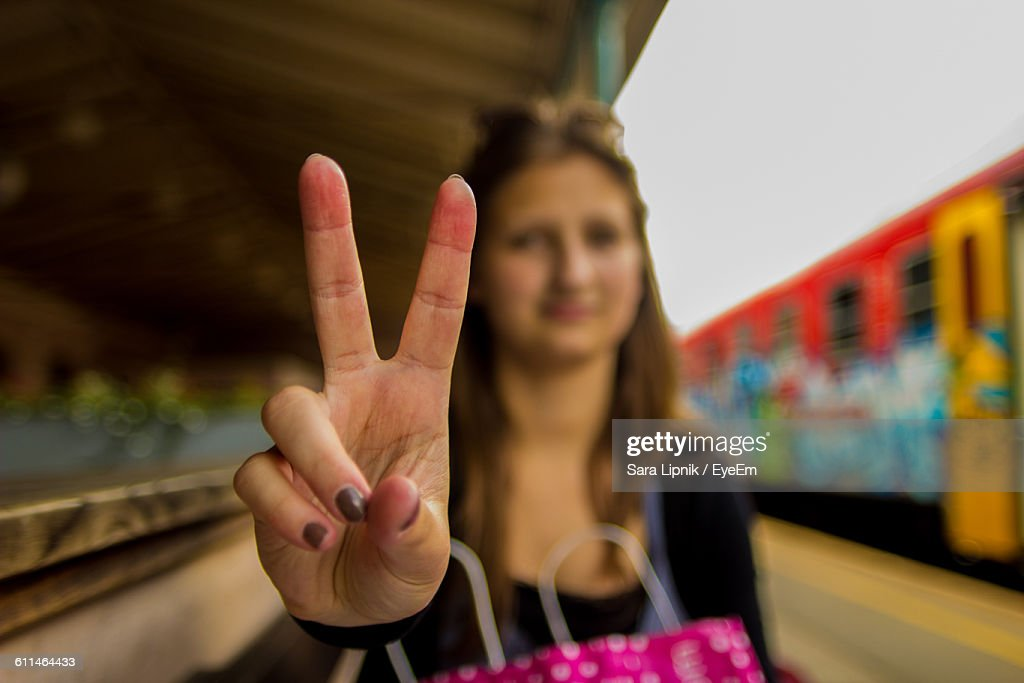 Close-Up Of Woman Gesturing Peace Sign While Standing At Railroad Station