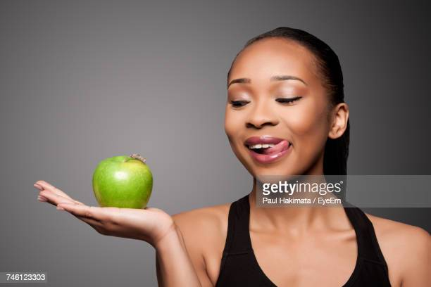 Close-Up Of Woman Holding Apple Against Gray Background