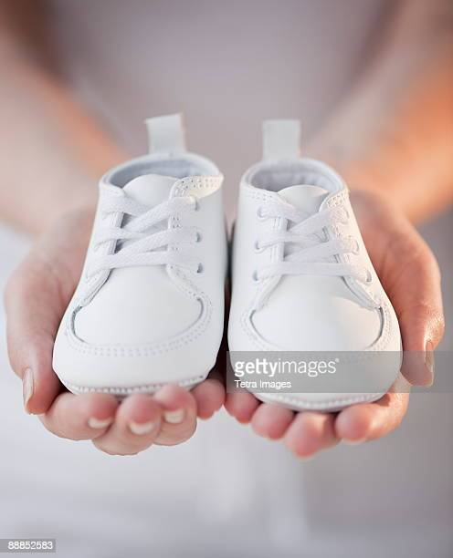 Close-up of woman holding baby shoes