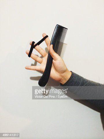 Close-up of woman holding comb and hair elastics
