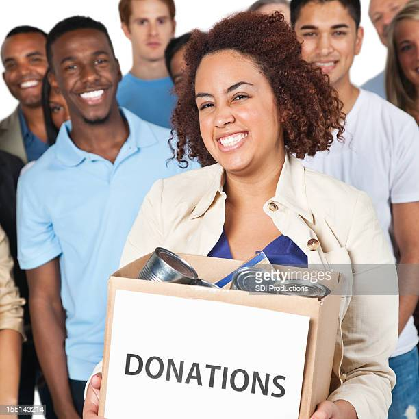 Closeup of woman holding donation box with people behind her
