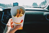 Close-Up Of Woman Holding French Fries In Car